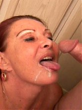 Slutty granny Blue Iris kneels down to give gramps a blowjob and gets her sprayed with cum live